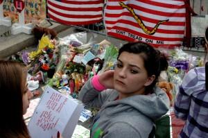 A woman holds back her emotions while visiting a makeshift memorial on Boylston Street several blocks east of the bombing sites in Boston, Massachusetts, on Thursday, April 18, 2013. (KEITH MACKENZIE PHOTO)